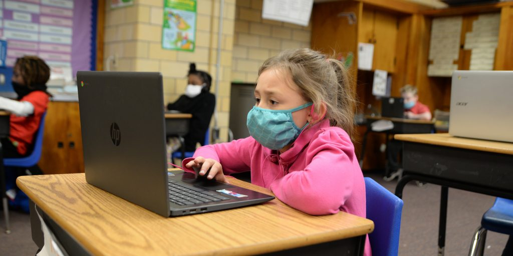Masked student sitting at desk with a laptop.